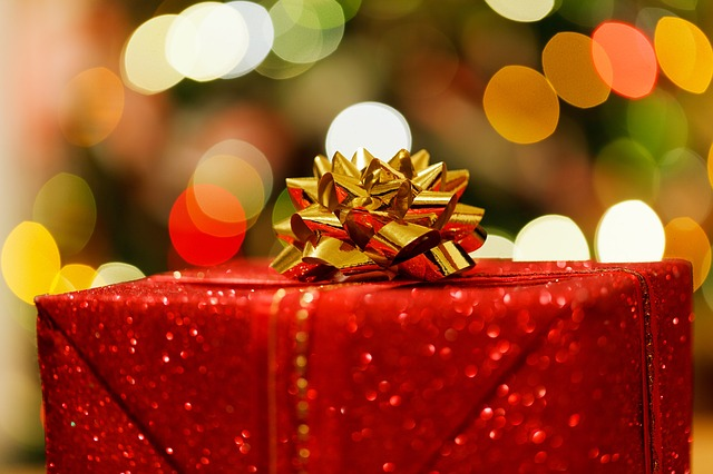 Christmas on a Budget with red wrapped gift under Christmas Tree.