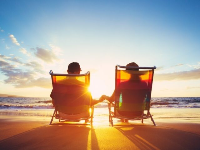Retired couple on the beach not worrying about social security benefits