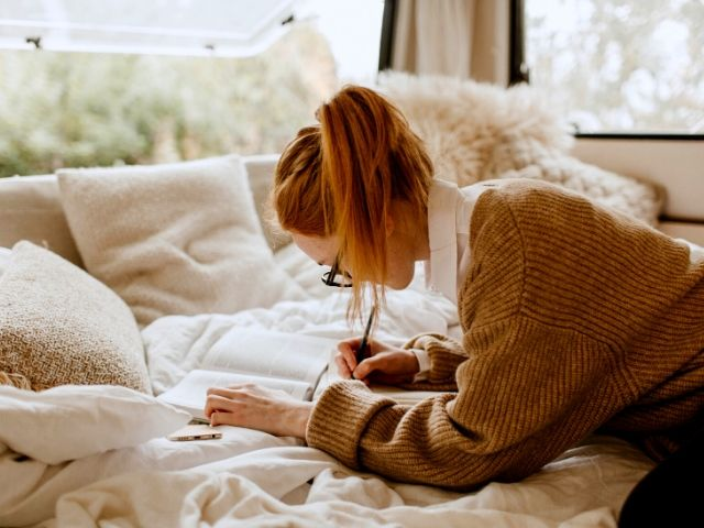 Tax Season Preparing make a list of deductions. A top tax tip with woman in golden sweater writing out tax deductions.