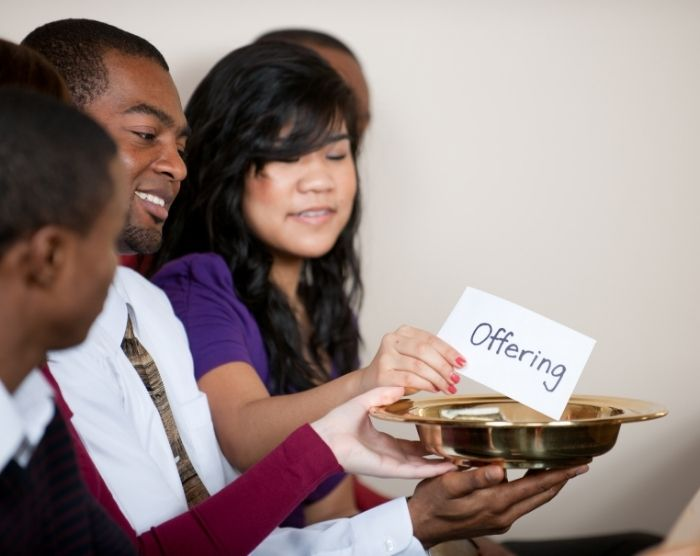 Tithing and taxes with church members putting money into offering plate