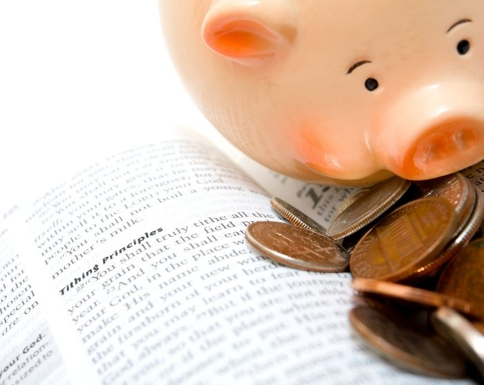 Tithing and taxes with piggybank next to tithing definition in book
