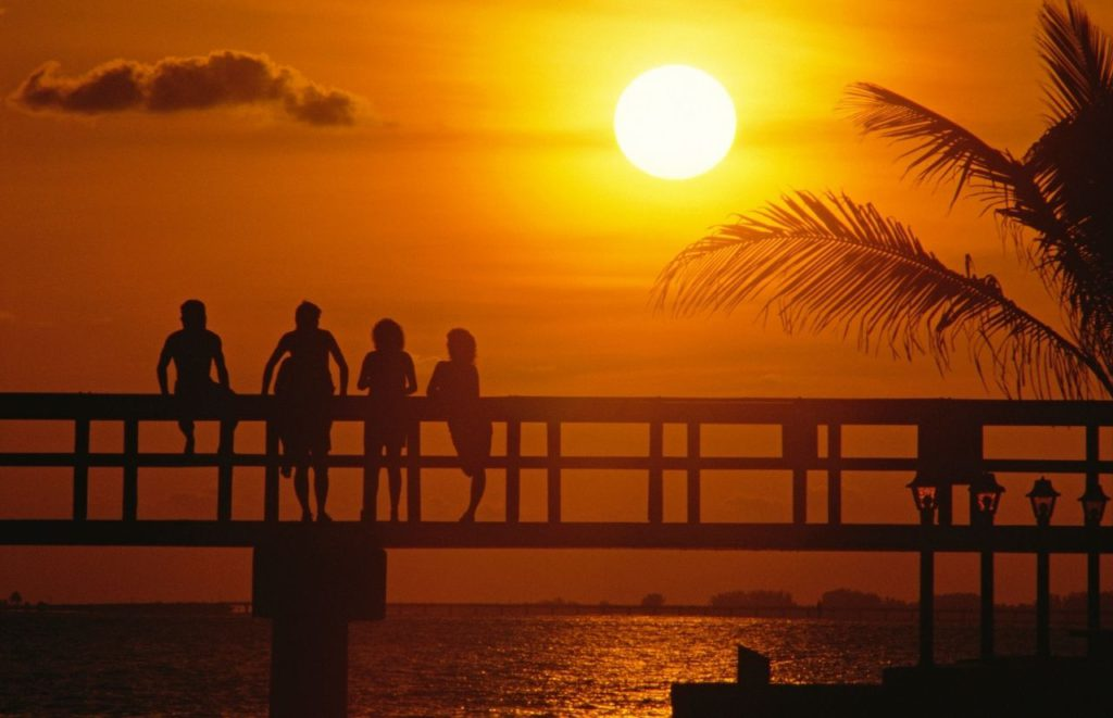 Florida sunset at beach with people on pier