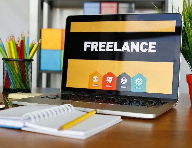 Freelance title on laptop with notepad and pencil